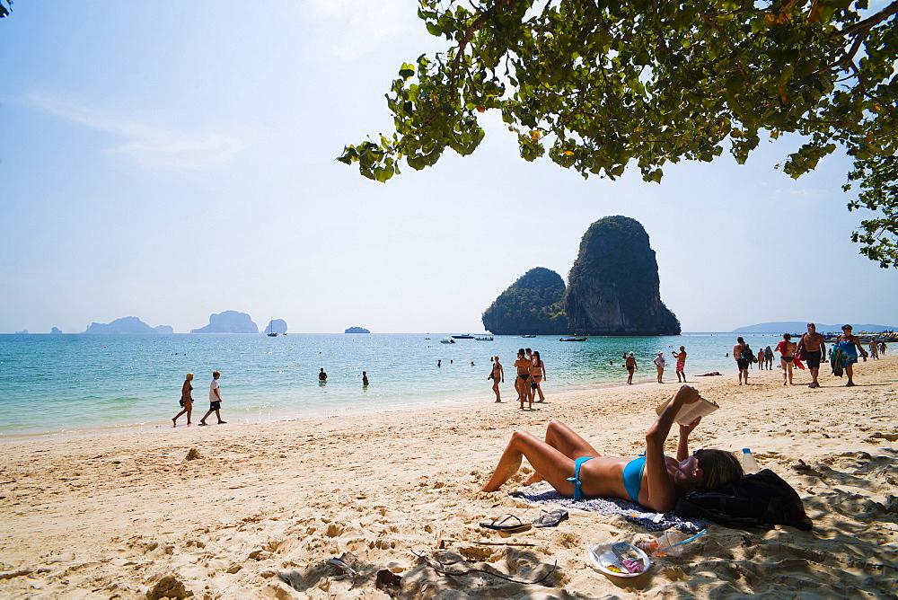 Tourist sunbathing and reading on Ao Phra Nang Beach, Railay (Rai Leh), South Thailand, Southeast Asia, Asia