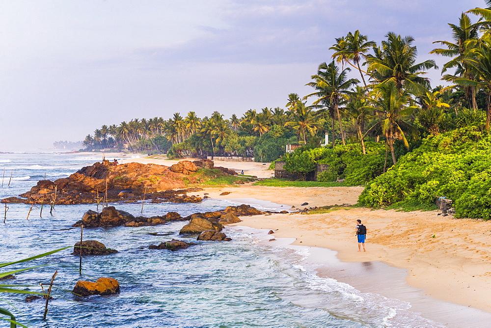 Tourist walking along Midigama Beach, near Weligama on the South Coast of Sri Lanka, Indian Ocean, Asia