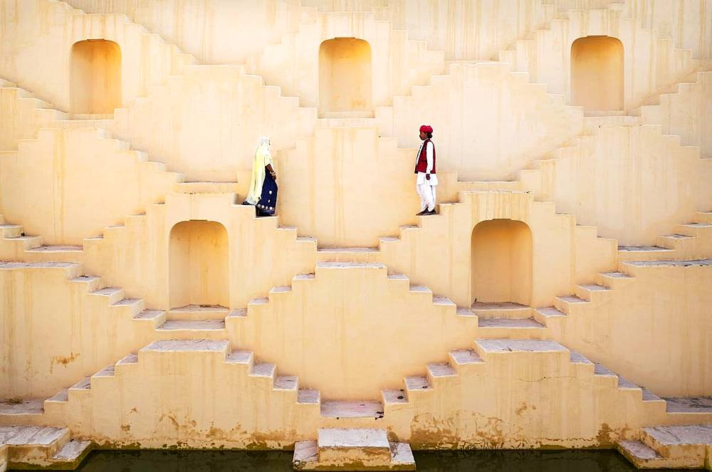 A Hindu man and woman dressed in traditional clothing, walk down the maze steps of Panna Meena ka Kund Stepwell, Amer, Rajasthan, India, Asia