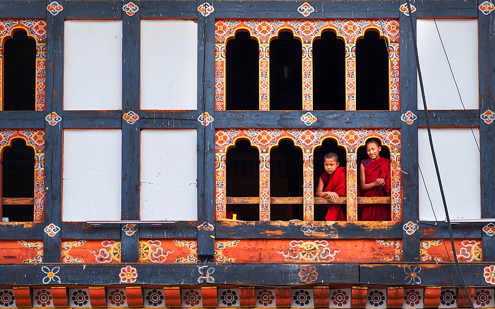 Bhutanese monks look through window frame, Kyichu Temple, Bhutan, Asia
