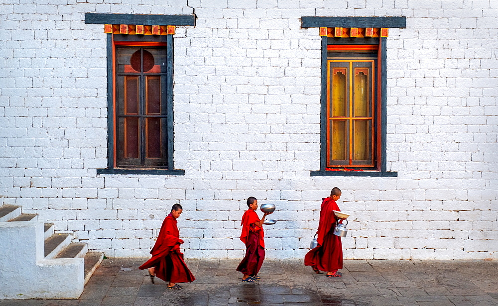 Three Buddhist monks carrying food bowls, Kyichu Temple.