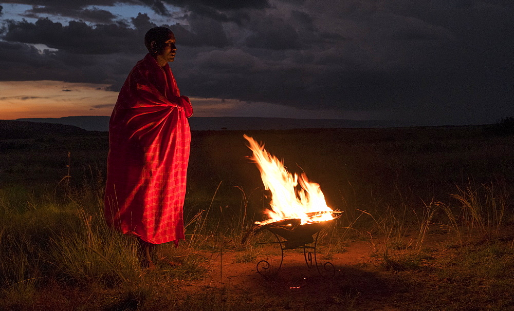 Masai Mara man wearing traditional tribal red blanket by camp fire, Masai Mara National Park, Kenya, East Africa, Africa