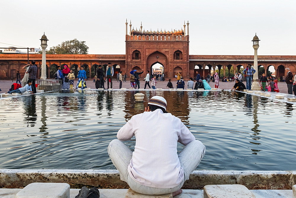 Muslim man washing hands and feet before prayer time, Jama Masjid, one of the largest mosques in India.