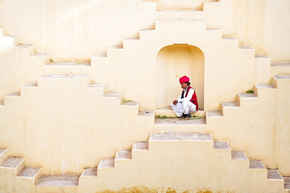 Man in Indian traditional clothing sitting in alcove on Panna Meena Ka Kund in Jaipur, India, Asia