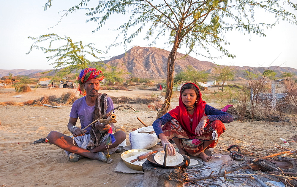 Hindu girl cooking while her father plays musical instrument in Pushkar, Rajasthan, India, Asia - 1111-70