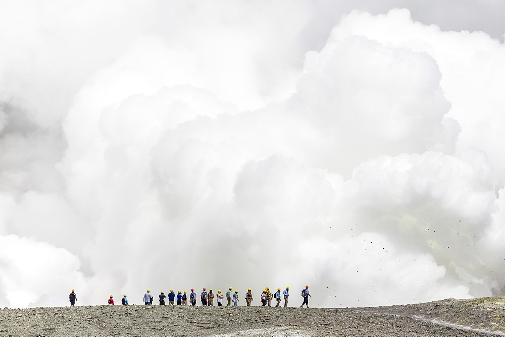 Visitors watching mud being ejected from the caldera floor of an active andesite stratovolcano on White Island, North Island, New Zealand, Pacific