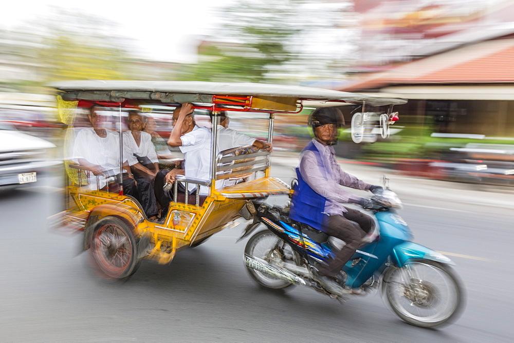 Motion blur image of a tuk-tuk in the capital city of Phnom Penh, Cambodia, Indochina, Southeast Asia, Asia