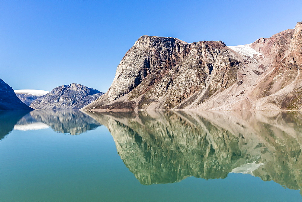Reflections on a calm sea of the steep cliffs of Icy Arm, Baffin Island, Nunavut, Canada, North America