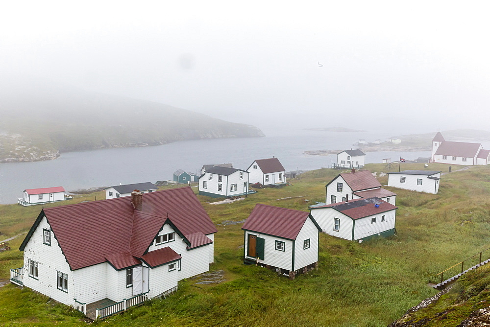 Fog rolls in over the small preserved fishing village of Battle Harbour, Labrador, Canada, North America