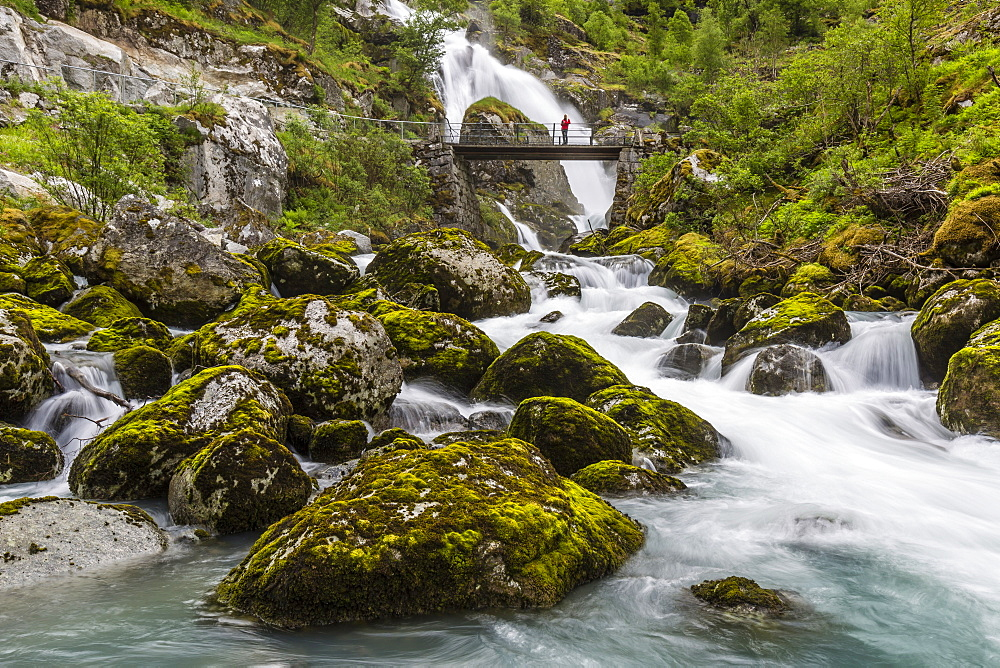 Slow shutter speed silky water of the Olden River and bridge as it flows along Briksdalen, Olden, Nordfjord, Norway, Scandinavia, Europe