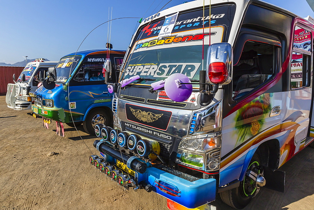 Highly decorated public buses in the busy port city of Larantuka, on Flores Island, Indonesia, Southeast Asia, Asia