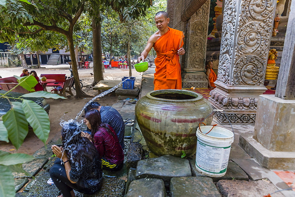 Buddhist monk offers water blessing near Prasat Bayon, Angkor Thom, Angkor, Siem Reap Province, Cambodia, Indochina, Southeast Asia, Asia