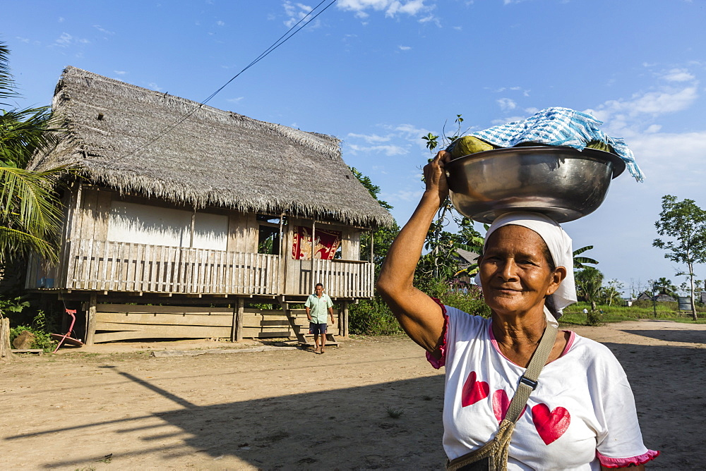 Woman carrying food in bowl, San Miguel Caño, Upper Amazon River Basin, Loreto, Peru, South America