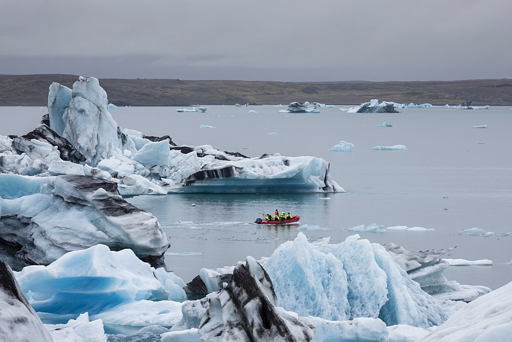 Boat amongst calved ice from the Breidamerkurjokull glacier in Jökulsárlón glacial lagoon, Iceland.