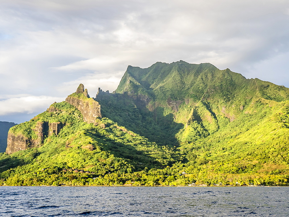 Sunrise approach to Cook Bay with the jagged outline of Mount Rotui, Moorea, Society Islands, French Polynesia, South Pacific, Pacific