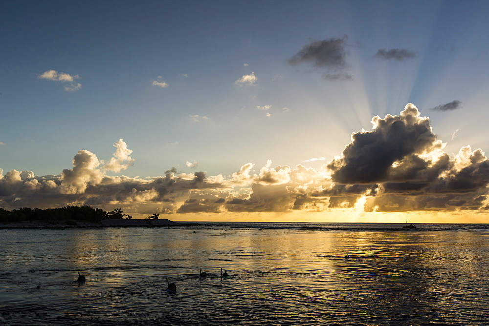 Snorkelers at sunset at Niau Atoll, Tuamotus, French Polynesia, South Pacific, Pacific