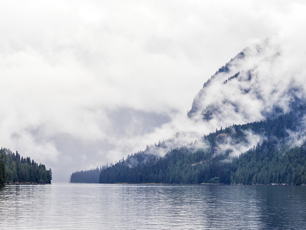 Low lying clouds shroud the mountain tops in Misty Fjords National Monument, Southeast Alaska, United States of America
