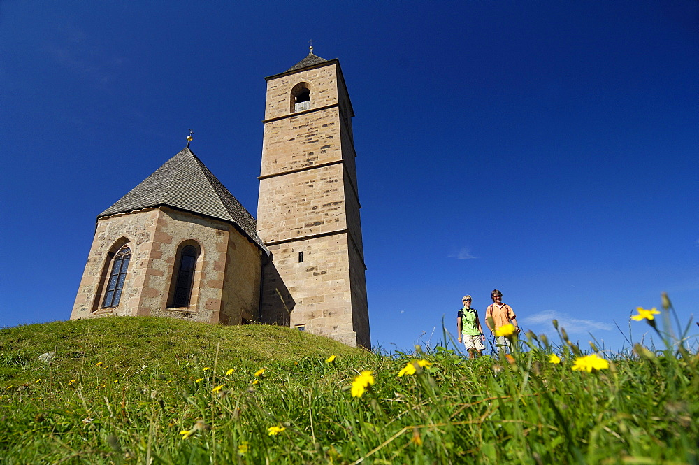 Hikers standing beside a church under blue sky, South Tyrol, Italy, Europe