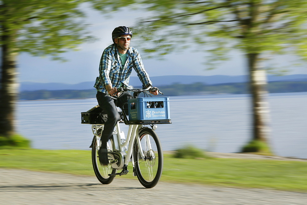 Man cycling with an E-bike along lake Starnberg, Upper Bavaria, Germany