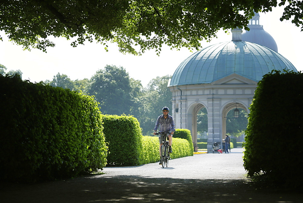 Man riding an e-bike through Hofgarten, Munich, Upper Bavaria, Germany