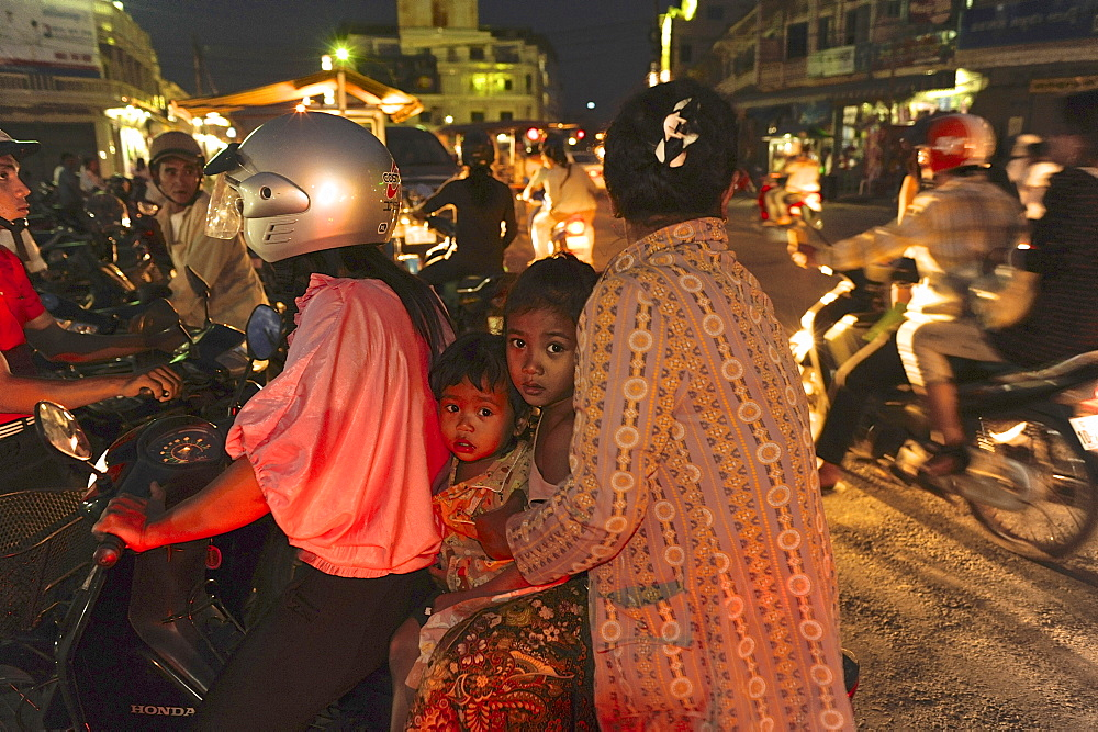 Two women with two children sitting on one motorscooter in the center of Battambang, Cambodia, Southeast Asia