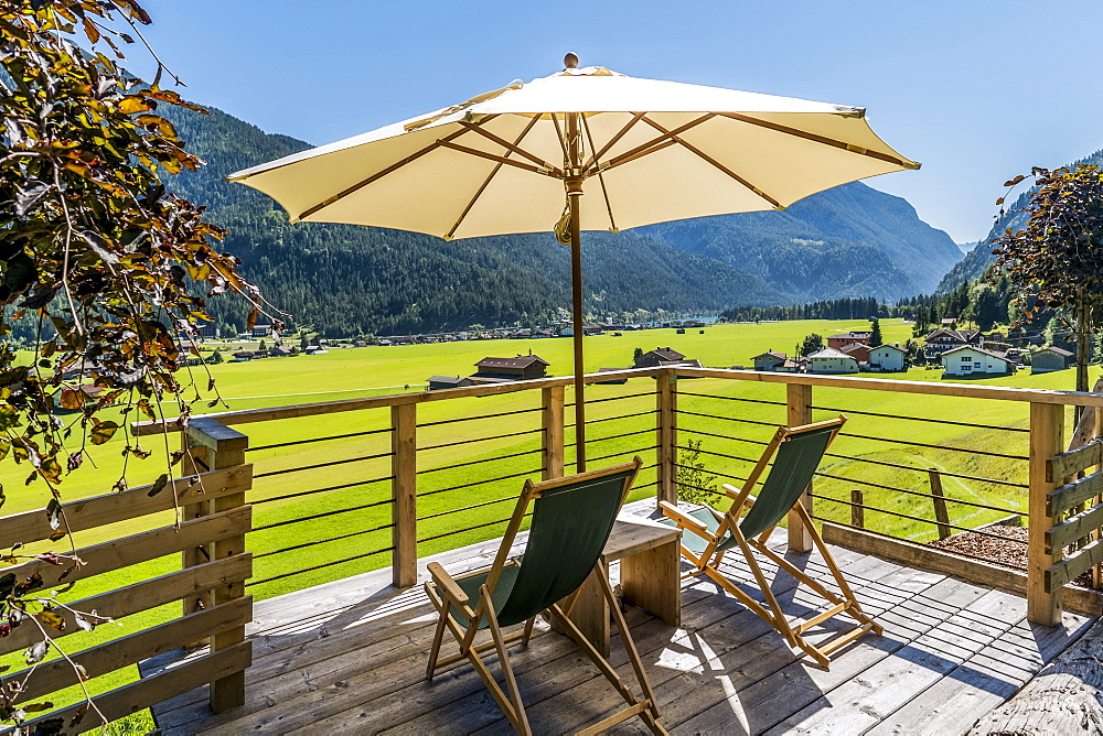 Deckchairs and sunshade on a terrace, lake Achensee and Achenkirch in background, Tyrol, Austria