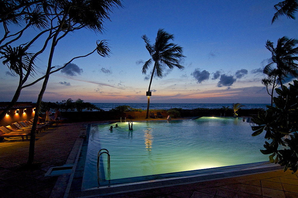 Pool overlooking the sea after sunset, Ranweli Holiday Village, Resort, Waikkal bei Negombo, Sri Lanka