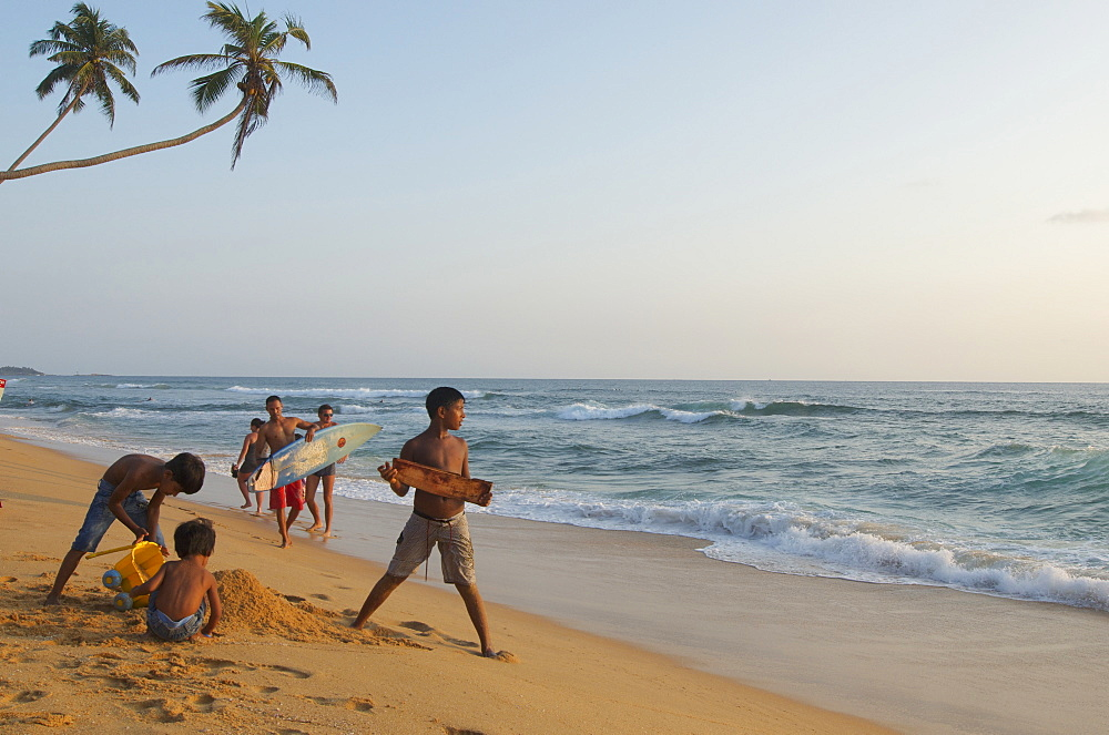Palm trees bending over the beach, Surfer and children on the beach in the early evening, Hikkaduwa, Southwest coast, Sri Lanka