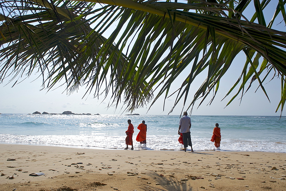 View through palm leaves towards the beach, buddhist novices at the sea, Hikkaduwa, Southwest coast, Sri Lanka