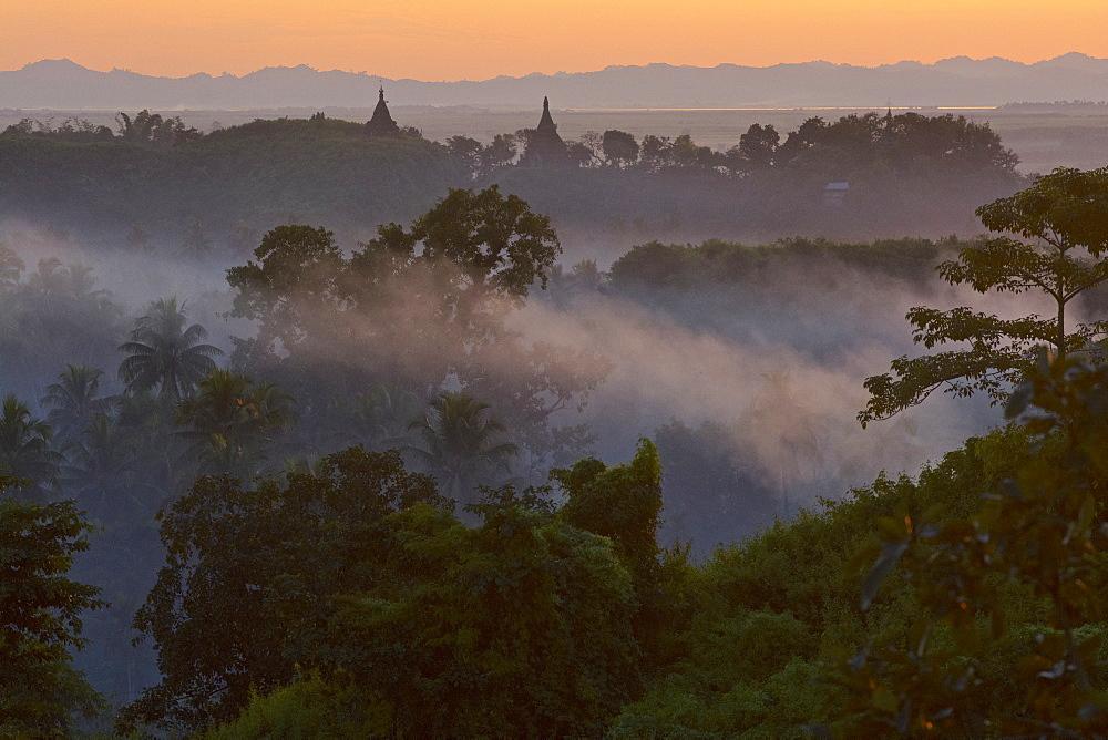 View above hill the hills and pagodas in the evening mist at Mrauk U, Myohaung north of Sittwe, Akyab, Rakhaing State, Arakan, Myanmar, Burma