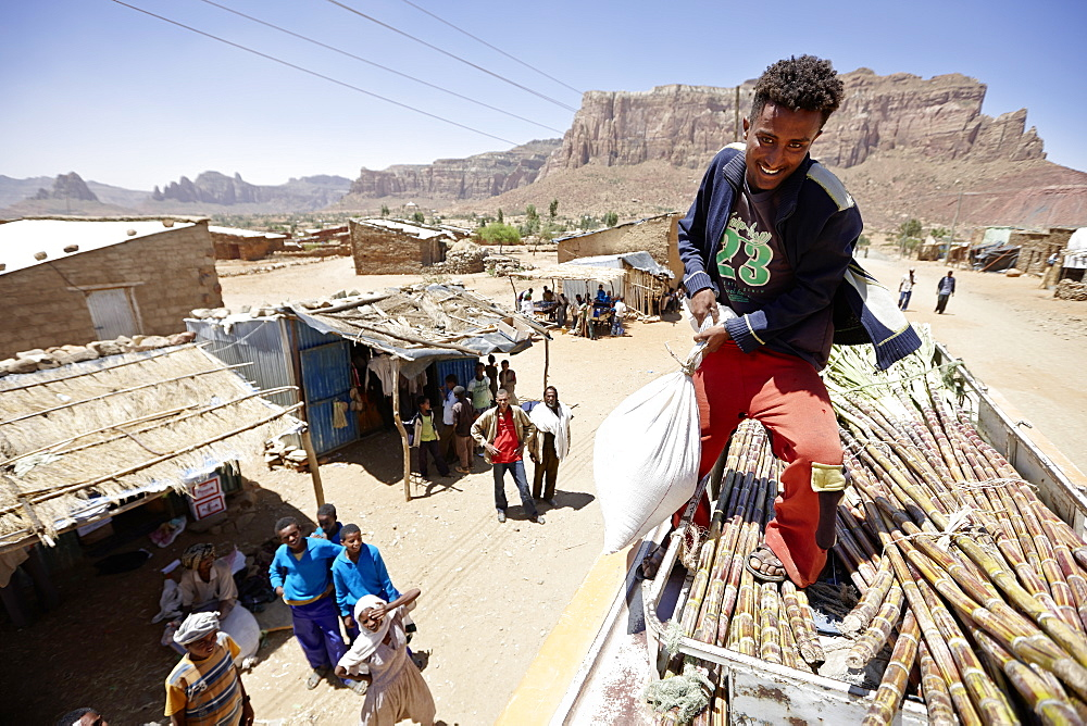 Loading of sugar cane and bags of grain on the roof of a cross-country coach, Gheralta mountains in background, Magab, Tigray region, Ethiopia