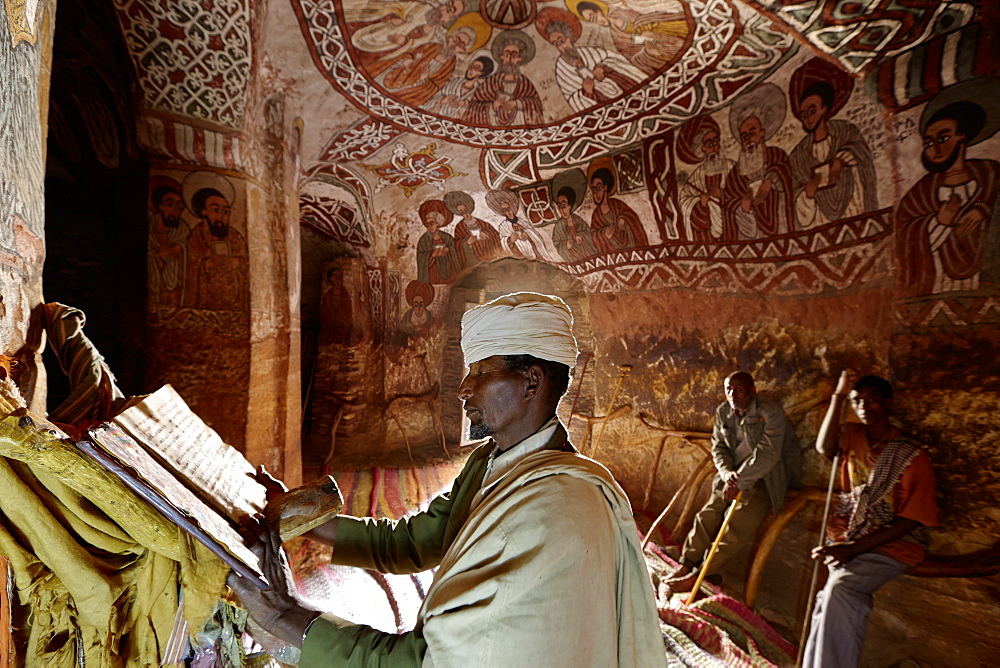Priest reading in an old goatskin manuscript, Abuna Yemata Guh church with mural painting, Hawzien, Tigray Region, Ethiopia