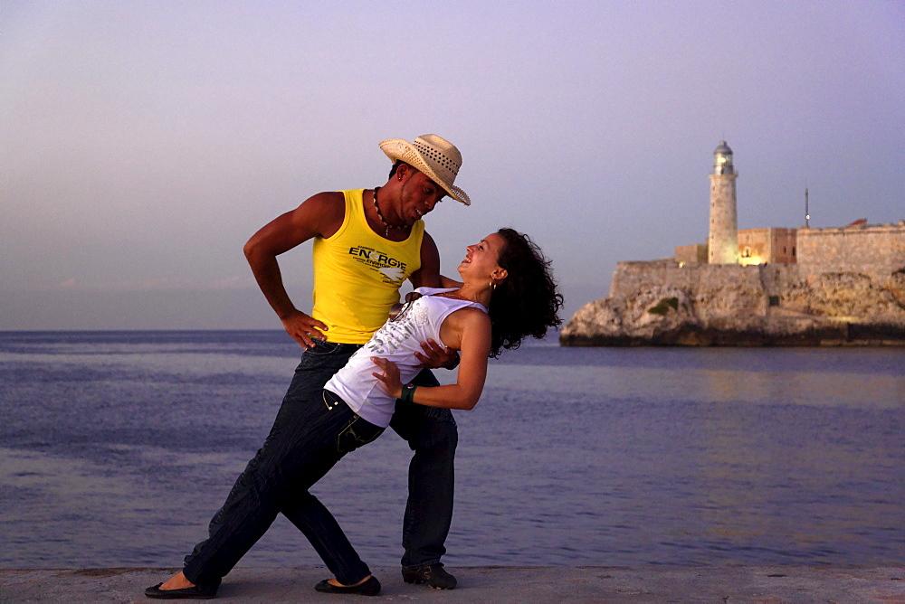 Couple dancing salsa, Castillo de los Tres Reyes del Morro in background, Havana, Ciudad de La Habana, Cuba, West Indies