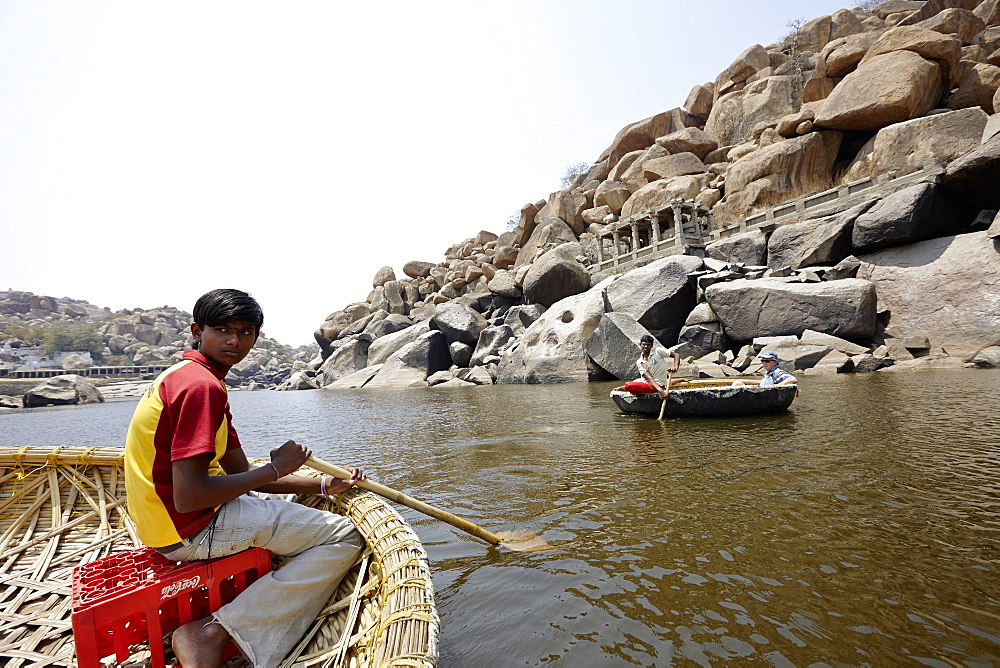 Boattrip in traditional round Coracle rowing boats, Tungabhadra River, Hampi, Karnataka, India