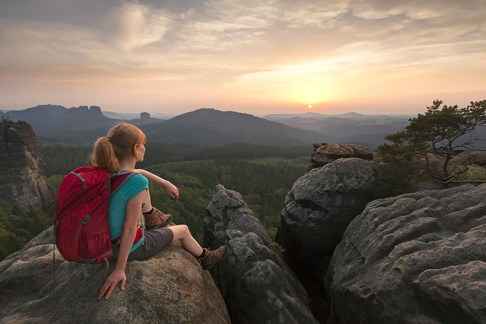 Young woman sitting on a rock while enjoying sunset, National Park Saxon Switzerland, Saxony, Germany