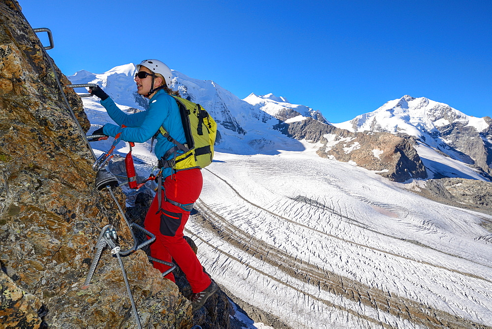 Woman climbing the via ferrata at Piz Trovat with view to Piz Palue (3905 m), Bellavista (3922 m), Piz Bernina (4049 m), and Per