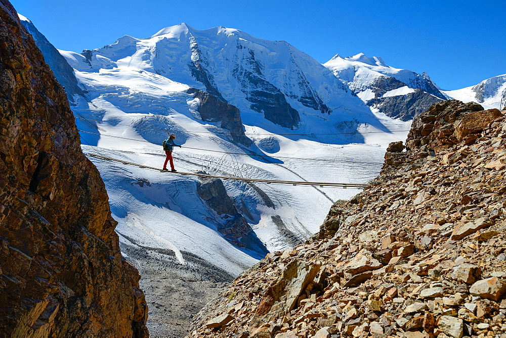 Woman on a suspension bridge climbing the via ferrata at Piz Trovat with view to Piz Palue (3905 m), Bellavista (3922 m) and Per