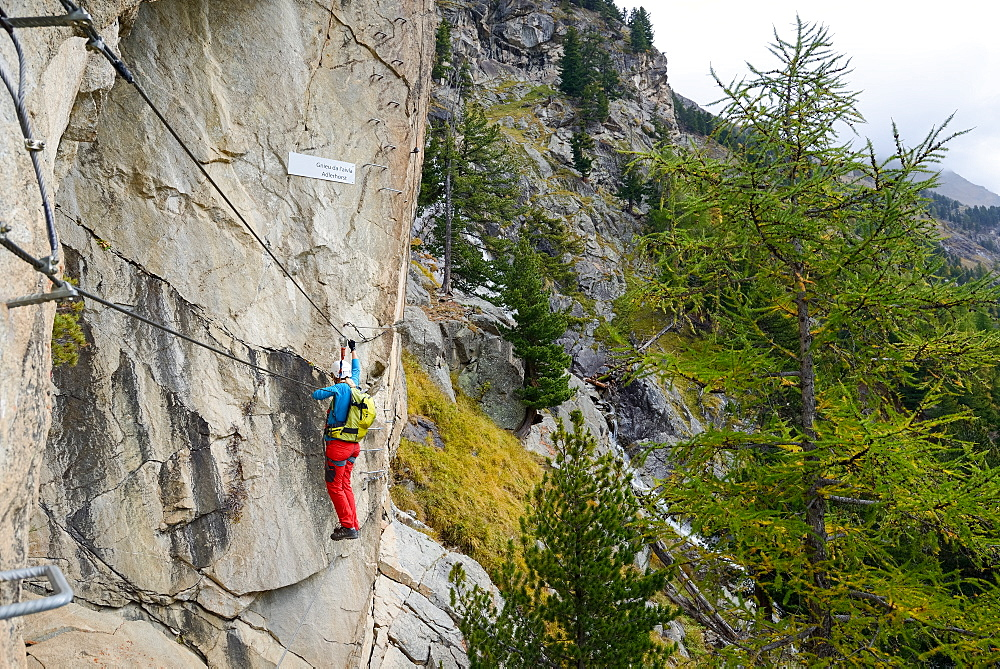 Woman climbing the via ferrata La Resgia, Engadin, Grisons, Switzerland