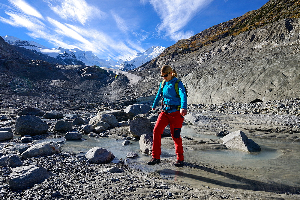 Woman crossing the Morteratsch Creek near the glacier mouth of Morteratsch glacier with view to Bellavista (3922 m), Piz Bernina