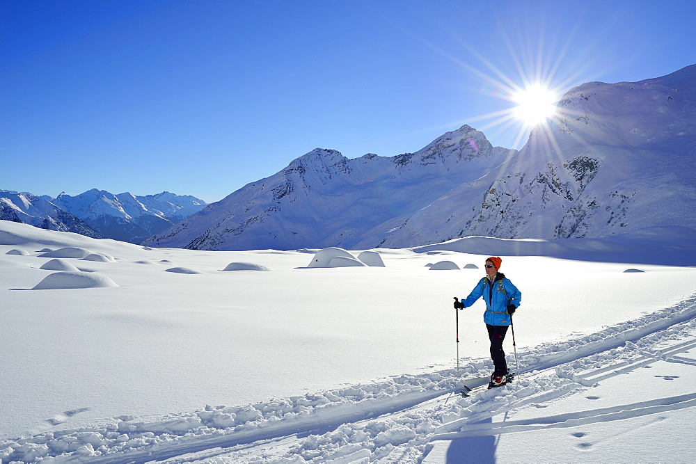 Female back-country skier ascending to Agglsspitze, Pflersch valley, Stubai Alps, South Tyrol, Italy