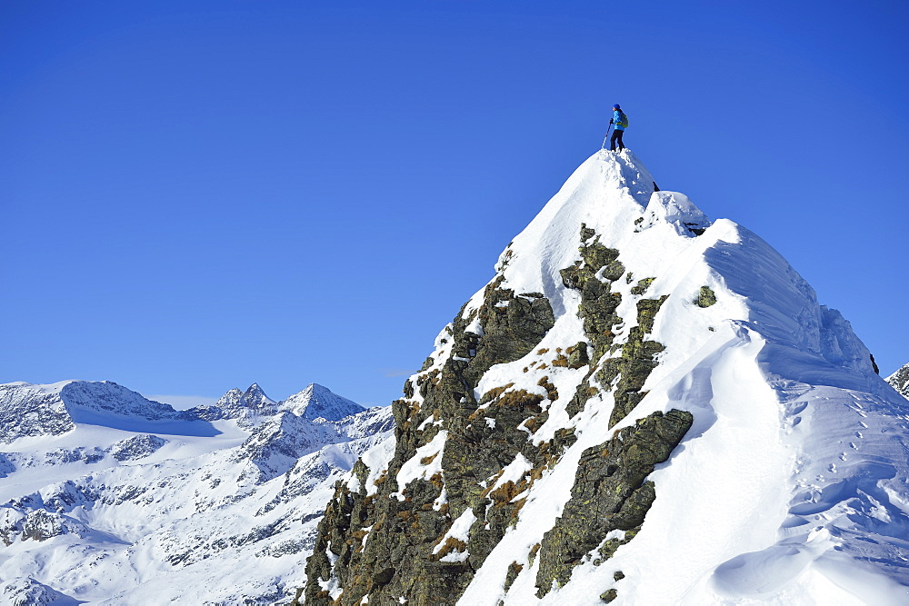 Female back-country skier standing on summit of Aeusseres Hocheck, Pflersch valley, Stubai Alps, South Tyrol, Italy