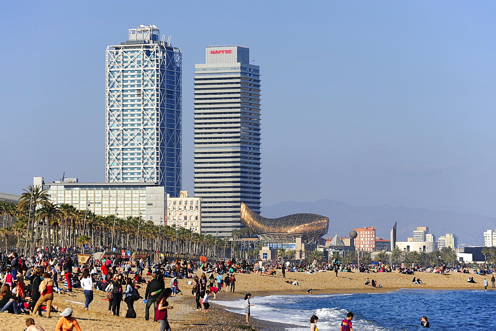 People on Barceloneta beach, with a view towards the skyscrapers Hotel Arts and Torre Mapfre, Vila Olimpica, Port Olimpic at the