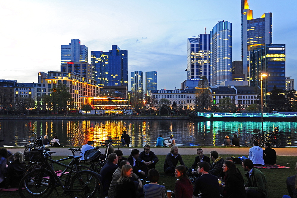 People along the banks of the river in the evening, skyline of the banking district in the background, Frankfurt am Main, Hesse,