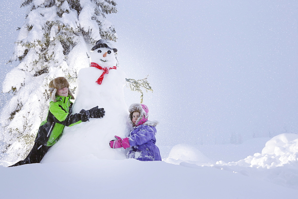 Children building a snowman, Passo Monte Croce di Comelico, South Tyrol, Italy