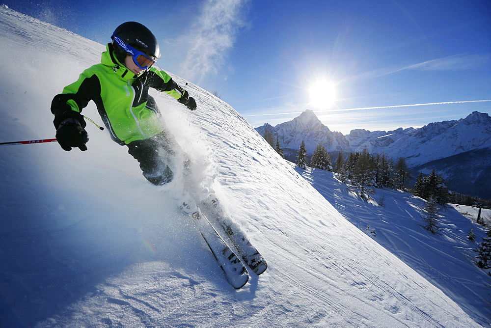 Boy downhill skiing from mount Helm (Monte Elmo), Sexten, South Tyrol, Italy