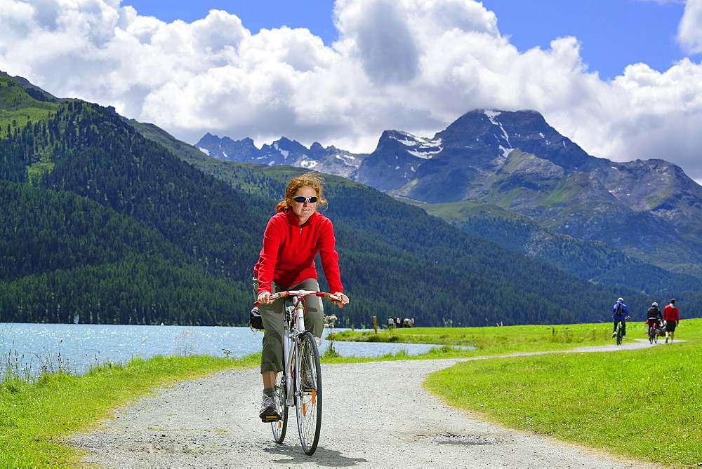 Woman cycling along Lake Silvaplana, Upper Engadin, Engadin, Canton of Graubuenden, Switzerland