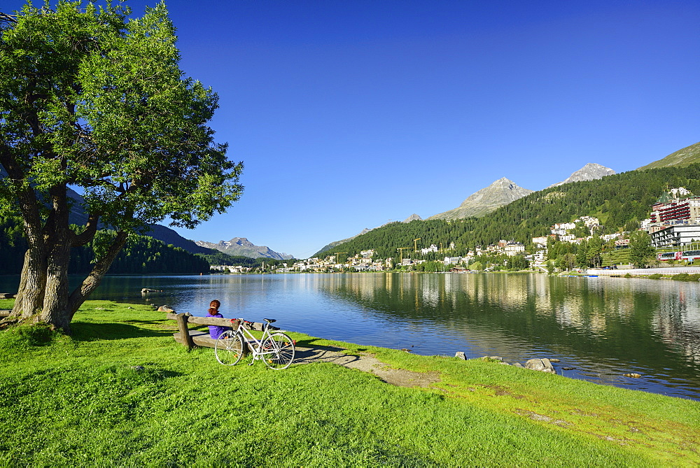 Cyclist resting on a bench at Lake St. Moritz, St. Moritz, Upper Engadin, Kanton of Graubuenden, Switzerland