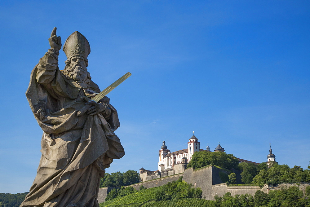 Statue on Alte Mainbruecke bridge across the Main river with Marienberg fortress on the hillside, Wuerzburg, Franconia, Bavaria,