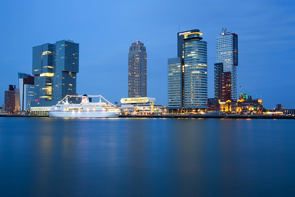 Cruise ship MS Deutschland (Reederei Peter Deilmann) at Rotterdam Cruise Terminal on Nieuwe Maas river with high-rise buildings
