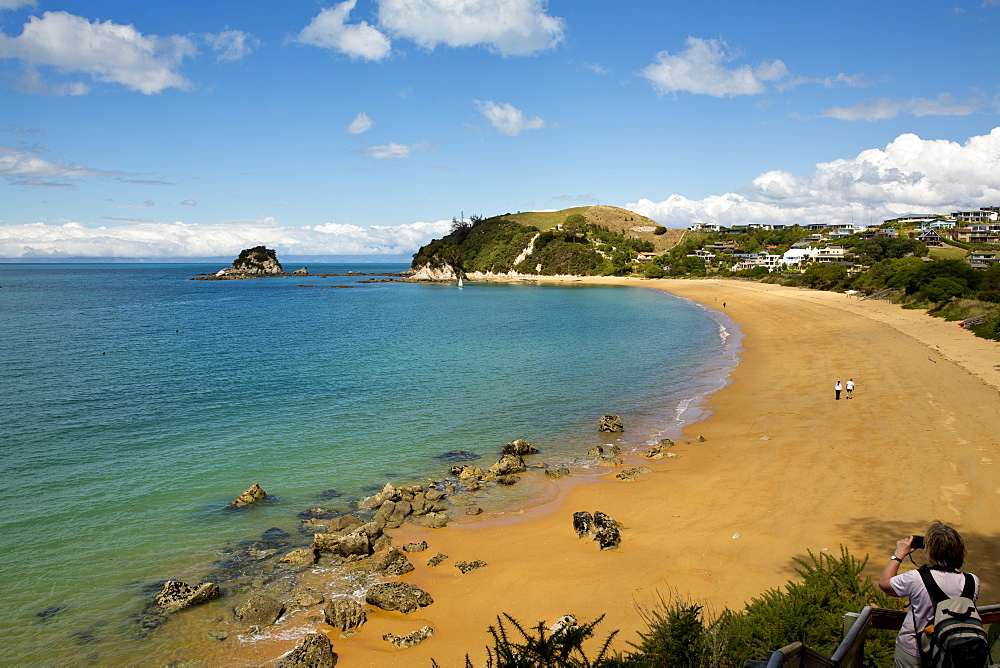 View of the sandy beach of Tasman Bay and Torlesse Rock on a sunny day at Abel Tasman National Park, near Kaiteriteri, Tasman Re